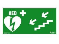 Znak AED w lewo schodami w dół