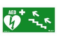 Znak AED w lewo schodami w górę